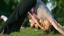 Yoga unter Anleitung auf der grünen Wiese: Angst und Depressionen schwinden.
