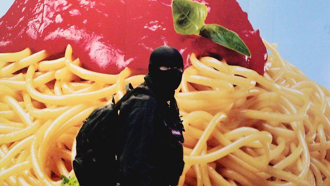 Das Mitglied einer Anti-Mafia-Einheit steht in Neapel vor einem Werbeplakat.