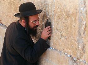 Ein Jude hält sein Mobiltelefon an die Klagemauer in Jerusalem - am anderen Ende der Leitung ist ein Freund aus Frankreich.