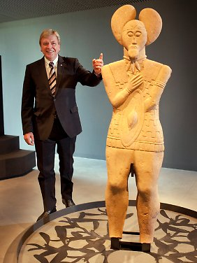 """Landesfürst neben Keltenfürst: Hessens Ministerpräsident Bouffier neben der steinernen Skulptur des sogenannten """"Keltenfürsten"""", die Hauptattraktion im neuen Museum."""