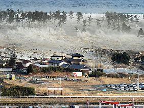 Die Tsunami-Welle trifft auf die Küste der Präfektur Miyagi.