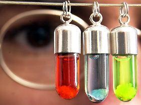 Ein Molekularbiologe begutachtet DNA-Fäden in kleinen Glasanhängern.