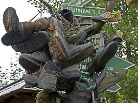 """Wanderschuhe an einem Wegweiser im ostthüringischen Blankenstein am """"Kilometer Null"""" des 168,3 Kilometer langen Rennsteig-Wanderweges."""