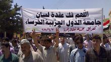 """Syrische Demonstranten marschieren durch das Dorf Kfar-Nebel. """"Möge Gott die Stille des der Arabischen Liga beenden"""", steht sinngemäß auf dem Banner."""