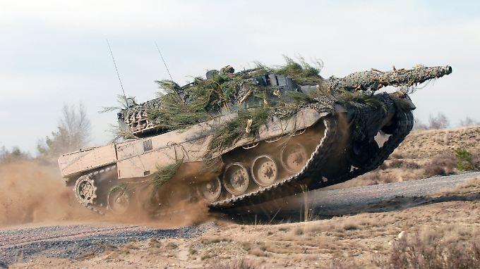 Kampfpanzer vom Typ Leopard 2 in voller Fahrt auf einem Testgelände.