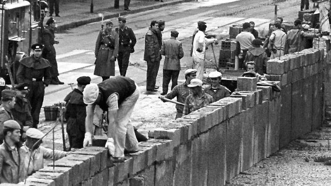 """Unter der Aufsicht von Volkspolizisten bauen Ostberliner Maurer am Potsdamer Platz am """"Antifaschistischen Schutzwall"""" (Bild vom 18. August 1961)."""