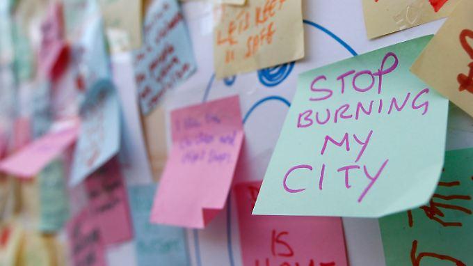 """""""Hört auf, meine Stadt abzubrennen"""": Zettel an einem zerstörten Geschäft im Londoner Stadtteil Peckham."""