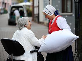 """Volksnahe Märchenfigur: Als """"Frau Holle"""" spricht Marlu Stoffels in Hessisch Lichtenau mit einer Passantin."""
