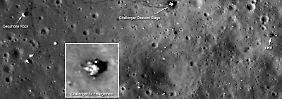 """Die Aufnahme des Landeplatzes der Apollo-17-Mission zeigt die Fussspuren der Astronauten (dunkle Linien), die Position des Instrumentenpakets der ALSEP-Messstation (Pfeil oben l.), die Spuren des Mondbuggys (hellere parallele Linien) und das Landemodul """"Challenger"""" (Pfeil """"Challenger Descent Stage"""" sowie eine vergrößerte Darstellung im Kasten unten l.)."""