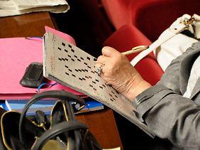 Während der Debatte über die Griechenland-Hilfe in der französischen Nationalversammlung löst eine Abgeordnete ein Kreuzworträtsel.