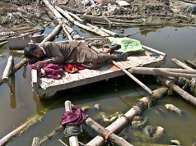 Ein Mann schläft auf den Trümmern seines durch die Fluten zerstörten Hauses in Nowshera, Pakistan.