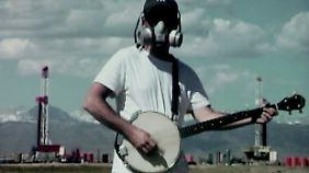 Mit Gasmaske und Banjo auf der Suche nach Antworten.