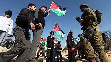 Israelische Soldaten stehen palästinensischen Demonstranten nahe der Siedlung Beit Omar gegenüber.