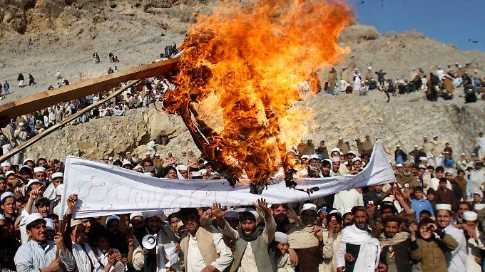 Vor der Militärbasis in Ghani Khail, östlich von Kabul, verbrennen aufgebrachte Menschen eine Obama-Puppe