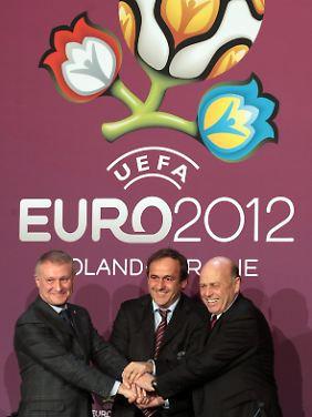 Posen für die Fotografen: Uefa-Präsident Michel Platini (M), der ukrainische Fußballchef Grigori Surkis (l.) und Polens Verbandschef Gregorz Lato 2009 beim gemeinsamen EM-Händedruck.