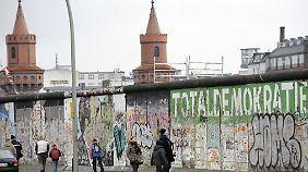 An der East Side Gallery, im Hintergrund die Türme der Oberbaumbrücke. Die Mauer an der Mühlenstraße wurde Anfang 1990 von etwa 118 Künstlern aus aller Welt bemalt.