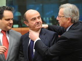 Ist es ein Scherz oder sind es die Nerven? Spaniens Wirtschaftsminister Luis de Guindos ist sich bei Juncker nicht ganz sicher.