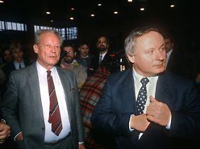 """Brandt und sein """"Lieblingsenkel"""" Lafontaine bei einem Frühlingstreffen der SPD in Norderstedt am 21. März 1987. An diesem Samstag machte Brandt erneut deutlich, dass er Lafontaine gern als seinen Nachfolger sehen würde."""