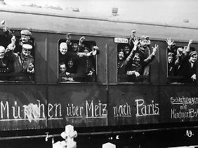 Mobilmachung im August 1914 in Deutschland: Soldaten winken im Glauben an einen schnellen Sieg aus dem Zug, der sie an die Front bringt.