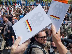 Mit in die Höhe gehaltenen Grundgesetzen wollen die Demonstranten auf ihr Recht auf Versammlungsfreiheit aufmerksam machen.