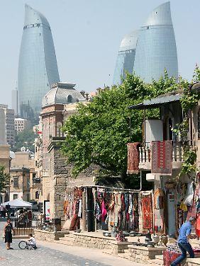 Teppiche hängen vor einem Geschäft in der Altstadt von Baku; im Hintergrund ragen die Flametowers in den Himmel.