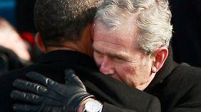 """George W. Bush umarmt Obama nach dessen Amtseid, der vom """"President-elect"""" zum """"President"""" wird."""