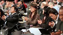 Die chinesische Delegation klatscht - China ist mit der windelweichen Vereinbarung zufrieden.