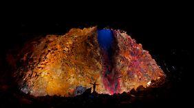 Die Magmakammer des Vulkans ist 120 Meter hoch. Scheinwerfer strahlen die in vielen Farben schillernden Wände an.