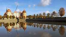 Das Jagdschlosses Moritzburg bei Dresden spiegelt sich im Wasser.