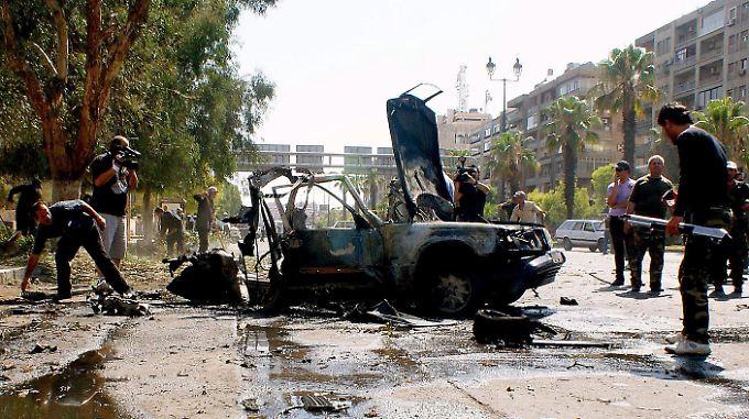 Das Bild der staatlichen Nachrichtenagentur Sana zeigt Polizisten, die ein Auto untersuchen, dass in Damaskus explodierte.