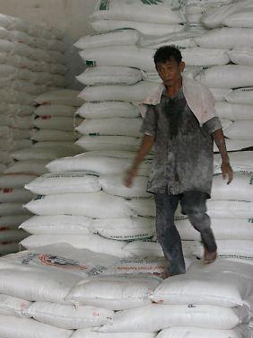 Alles auf Zucker: Ein Arbeiter läuft in einer Lagerhalle in Djakarta, Indonesien, über einen Stapel von Zucker-Säcken.