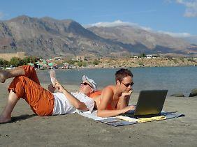 Muss nur noch kurz die Welt retten: Wer mit den Gedanken oder per Laptop und Handy noch halb im Job festhängt, erholt sich im Urlaub weniger.