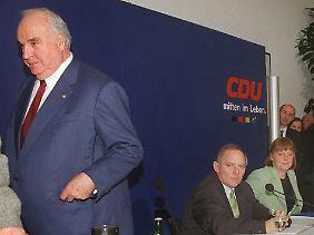 30. November 1999, der Bruch steht kurz bevor: Ex-Kanzler Kohl verlässt eine Pressekonferenz zur CDU-Spendenaffäre und lässt Schäuble und Merkel sitzen.