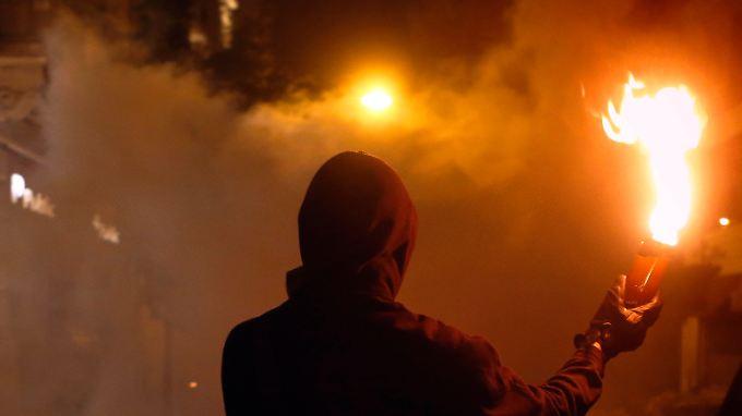 """Erst der Regen vertreibt die zum Teil gewalttätigen Protestler vor dem Parlament in Athen. Dann folgt das """"Ja"""" der Abgeordnet"""
