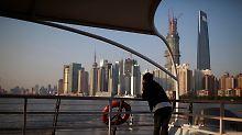 Rasant wachsende Metropole: Nachdenklich blickt dieser junge Mann über den Huangpu auf die Skyline von Shanghai.