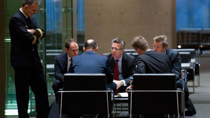De Maizière berät sich mit seinen Mitarbeitern.