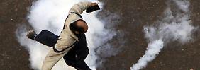 Unruhen am Wochenende: Ein Demonstrant tritt gegen eine Tränengasbombe.