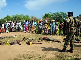 Dorfbewohner und Polizisten vor getöteten Pokomo-Angreifern.
