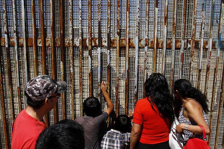 Mexikanische Einwohner unterhalten sich mit ihren Verwandten auf der anderen Seite des Zauns, der die USA von Mexiko trennt. Hier in Playas Tijuana ist die von Donald Trump geforderte Mauer schon Realität.