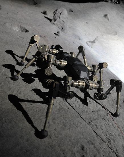 Zentimeter für Zentimeter krabbelt der Roboter durch den Mondkrater. Plötzlich gerät er auf dem steilen Hang leicht ins Rutschen. Eines seiner sechs Beine verfängt sich in einem tiefen Loch.