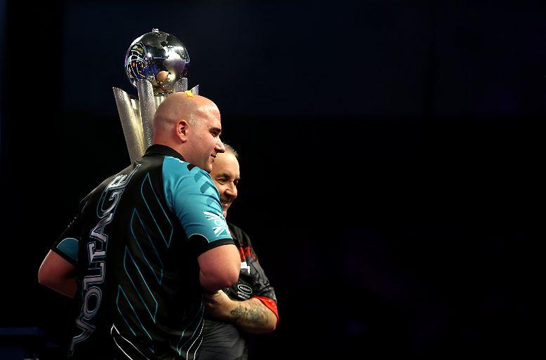 Sichtlich gerührt lässt sich der Rekordweltmeister nach dem 2:7 im WM-Finale gegen Rob Cross feiern, gemeinsam mit dem neuen Weltmeister reckt er den 3500 Fans die Trophäe entgegen. Und dann küsst er den Pokal ein letztes Mal.