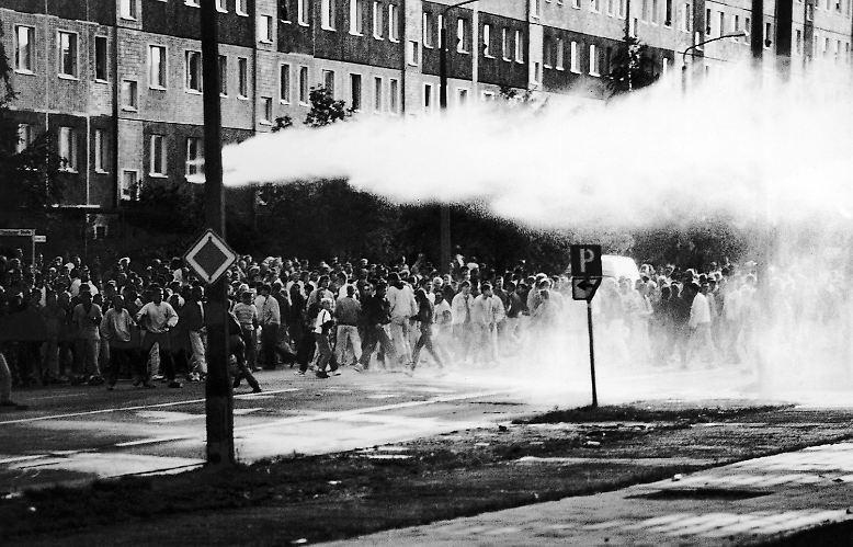 """Lichtenhagen im August 1992: Ein Mob versammelt sich vor dem """"Sonnenblumenhaus"""" im Rostocker Vorort Lichtenhagen ..."""