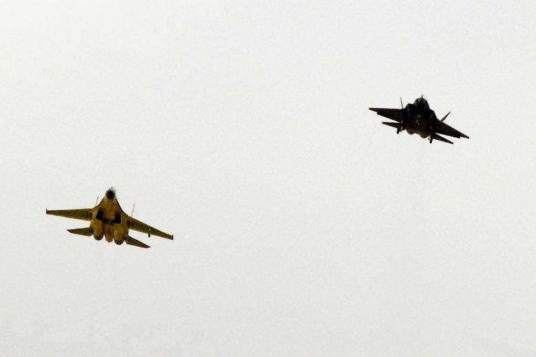 """In Fachkreisen sorgen diese Aufnahmen für erhebliches Aufsehen: Anfang 2012 November erscheinen in chinesischen Medien Bilder einer bislang unbekannten Maschine. An der Seite einer Shenyang J-11BS (links), so heißt es, absolviere ein """"Guying"""" genannter Stealth-Jet seinen Jungfernflug."""