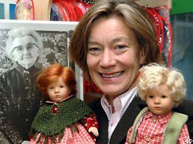 """Die Geschäftsführerin der """"Käthe-Kruse-Puppen"""", Andrea Kathrin Christenson, steht mit zwei Puppen in der Fabrik in Donauwörth."""